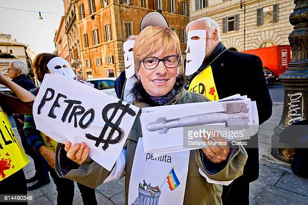 A protester with a mask of Defence Minister Roberta Pinotti with the missiles in one hand and in the other petrodollars during the No War Network...