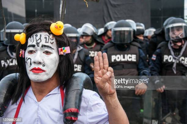 Protester with a painted face making the three finger salute in front of the riot policemen during the demonstration. Thousands of pro-democracy...