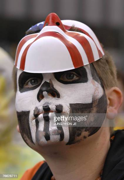 Protester with a painted face wears a mask during a rally against US President George W. Bush and APEC in Sydney, 08 September 2007, as the...