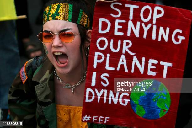 A protester with a placard that reads stop denying our planet is dying joins a demonstration organised by climate change activists from Extinction...