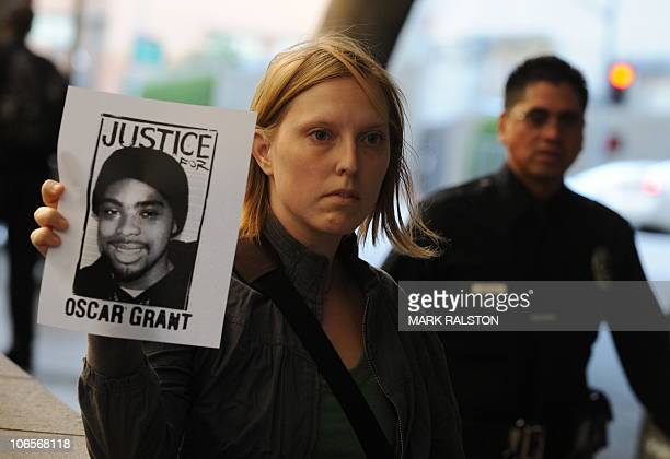 A protester with a portrait of slain transit passenger Oscar Grant stands outside the Los Angeles Superior Court before the sentencing of the former...