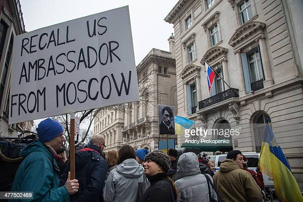 """Protester with a poster saying """"Recall US Ambassador from Moscow"""" during a mass demonstration against Russian troops invading Crimea, Ukraine, taken..."""