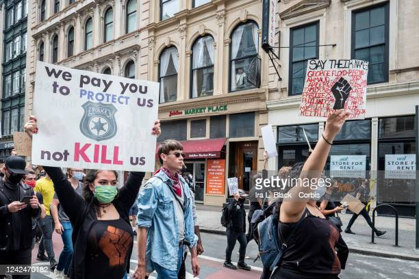 A protester with a sign over their head with a picture of a Police Badge and the saying We pay you to protest us not KILL us while another protester...