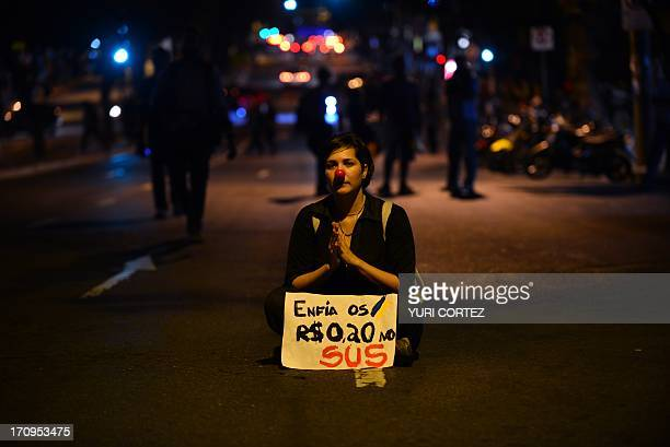 A protester with a sign reading 'put our 020 R$ in the health system' takes part in roadblock while protesting against corruption and price hikes on...