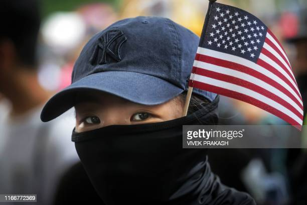 TOPSHOT A protester with a US national flag sticking out from her mask takes part in a march from Chater Garden to the US Consulate in Hong Kong on...