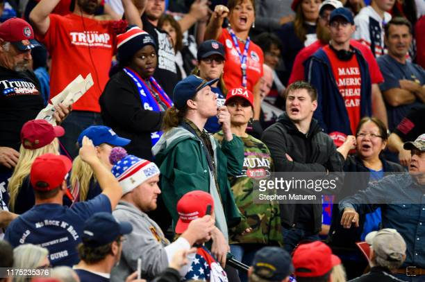 A protester with a whistle attempts to interrupt US President Donald Trump while he spoke during a campaign rally at the Target Center on October 10...