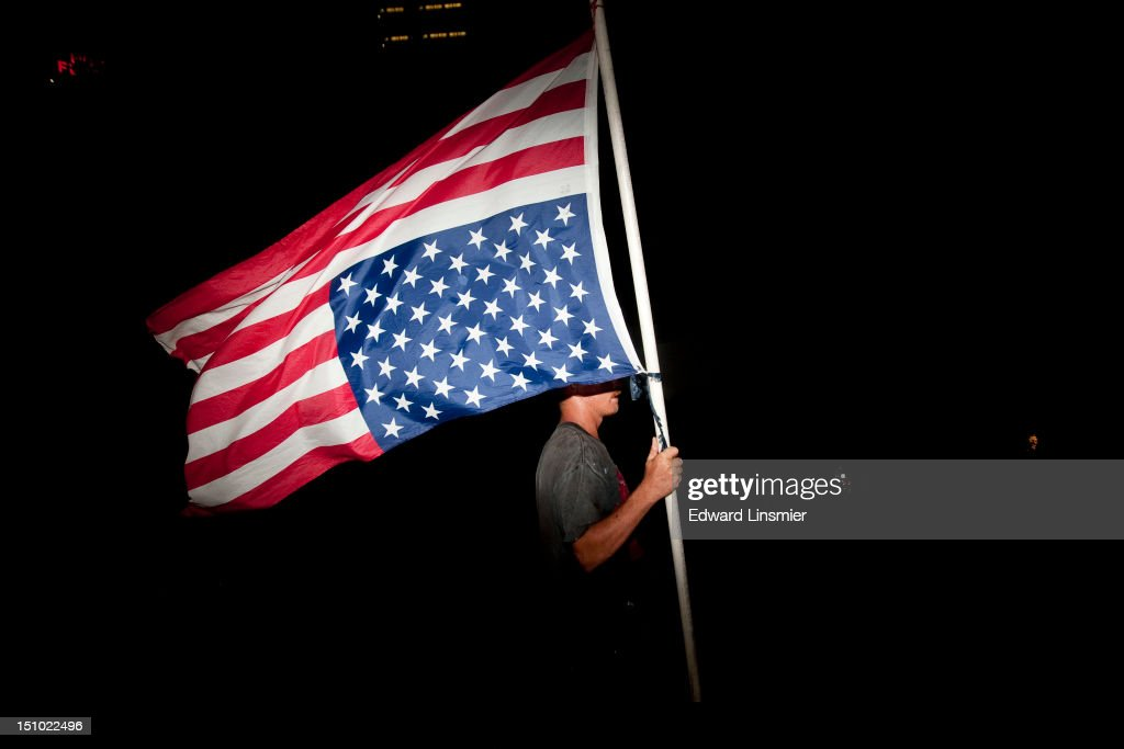 A protester with an upside-down American flag marches on the last night of the Republican National Convention in Tampa, Florida on August 30, 2012. The Republican party delegates affirmed Mitt Romney as the party's nominee for president August 28.