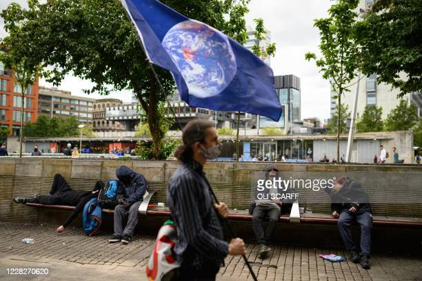 A protester with Extinction Rebellion holds an Earth flag as he stands next to men in an unconscious state in central Manchester on August 30 during...