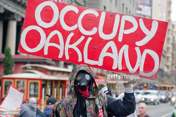 CONTENT] Protester with gas mask holding an Occupy Oakland sign at an Occupy protest on Black Friday in San Francisco demonstration demonstrator...