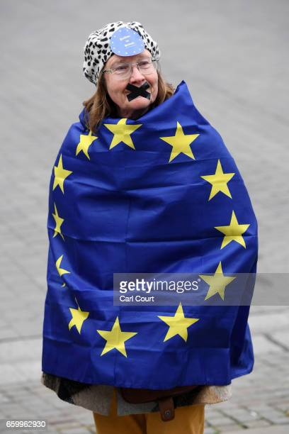 A protester with her mouth taped up wears a European Union flag as she takes part in a demonstration near parliament on March 29 2017 in London...
