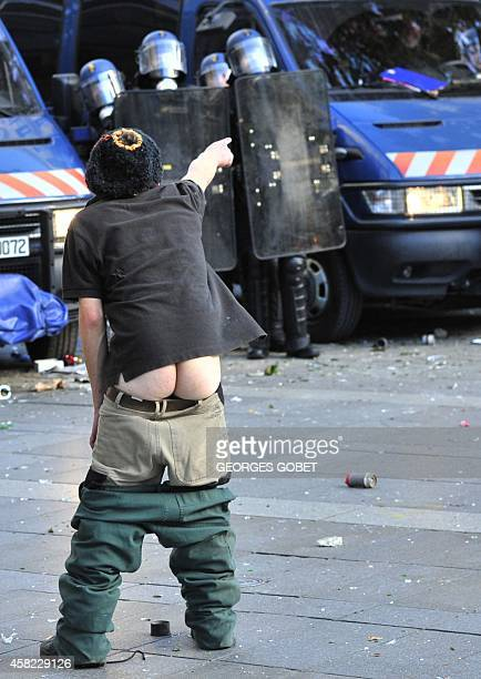 A protester with his pants pulled down gestures towards riot police on November 1 2014 in Nantes western France during a demonstration against police...