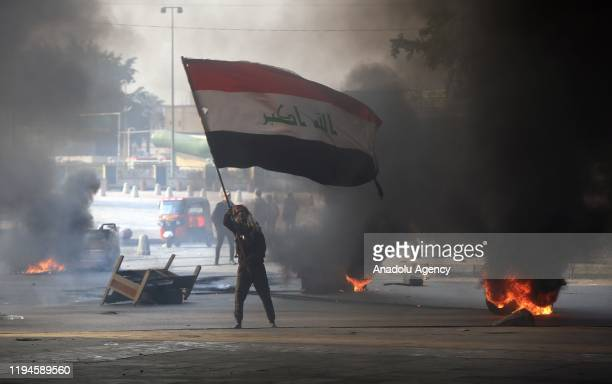 Protester with Iraqi flag is seen as he and other protesters burn tires to block the road during the anti-government demonstration at al-Tayaran...