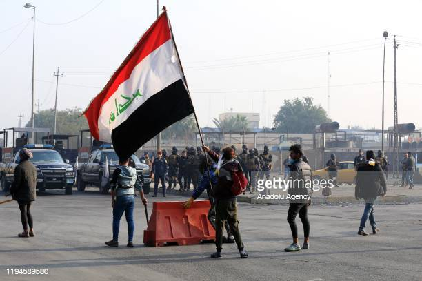 Protester with Iraqi flag is seen as he and other protesters put a barricade to block the road during the anti-government demonstration at al-Tayaran...