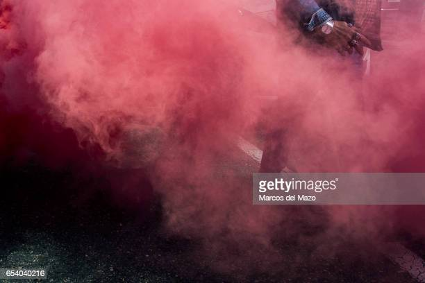 A protester with skull rings passing through a smoke bomb during a demonstration of taxi drivers against private services such us Uber and Cabify