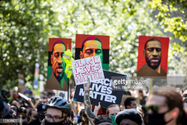 A protester with tattoos holds a sign that says Black Lives Matter with three painted portraits of George Floyd with the PanAfrican colors of Red...