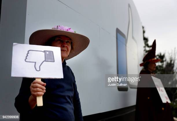 """Protester with the group """"Raging Grannies"""" holds a sign during a demonstration outside of Facebook headquarters on April 5, 2018 in Menlo Park,..."""