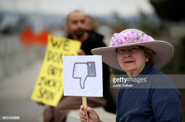 "Protester with the group ""Raging Grannies"" holds a sign during a demonstration outside of Facebook headquarters on April 5, 2018 in Menlo Park,..."