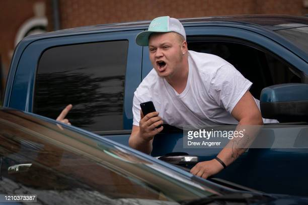 A protester with the group Reopen Maryland argues with another motorist while demonstrating near the State House to call on the state to lift the...