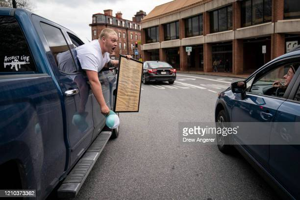 A protester with the group Reopen Maryland holds a copy of the US Constitution as he argues with another motorist while demonstrating near the State...