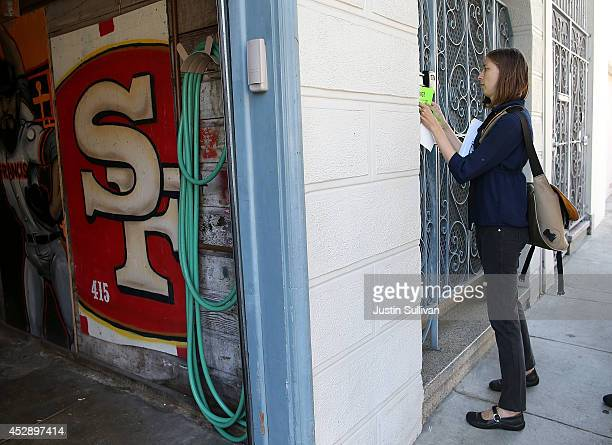 A protester with the San Francisco Tenant Union hangs a sign on a the exterior of a building during a demonstration outside of an apartment building...