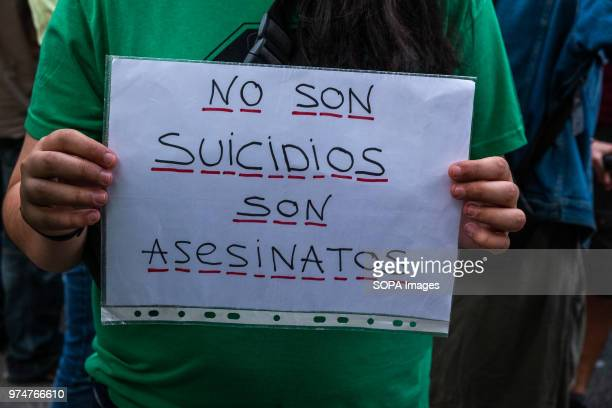 A protester with the traditional green shirt of STOP evictions shows a sign with the text 'They are not suicides they are murders' Hundreds of people...
