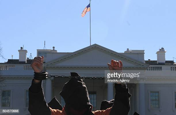 A protester worn orange jumpsuits those symbolize Guantanamo Bay detainees rises his handcuffed hands during a protest in front of the White House in...