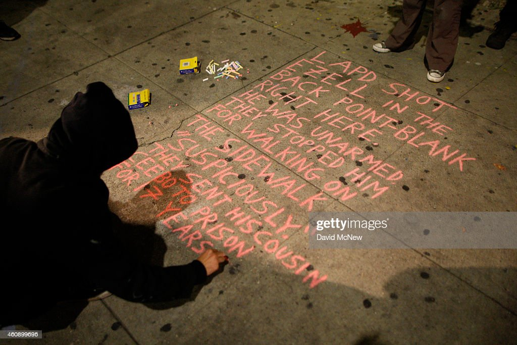 A protester writes a chalk message on the sidewalk near the site where Ezell Ford, a 25-year-old mentally ill black man, was shot and killed by two LAPD officers in August, on December 29, 2014 in Los Angeles, California. The long-awaited autopsy report, which was put on a security hold at the request of police and ordered by L.A. Mayor Eric Garcetti to be made public before the end of 2014, was released December 29.