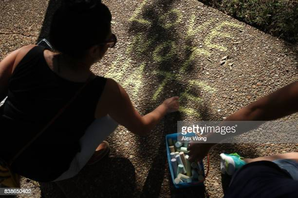 A protester writes a slogan with a piece of chalk on the sidewalk during a rally calling on the removal of a Confederate soldier statue on the...