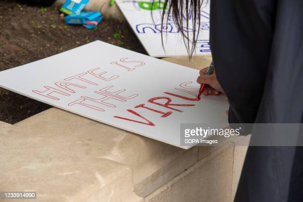 Protester writes Hate is the virus on a placard during a Stop Asian Hate protest at Parliament Square in London. Anti-Asian violence and abuse has...