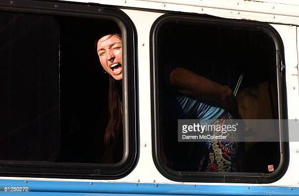 A protester yells out of a police bus window after being arrested at the corner of Fulton and Church Streets following an attempt to march from...
