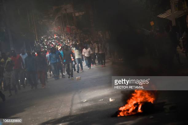 TOPSHOT Protesters activists and opposition party members walk past burning barricades during a protest demanding accountability from politicians for...