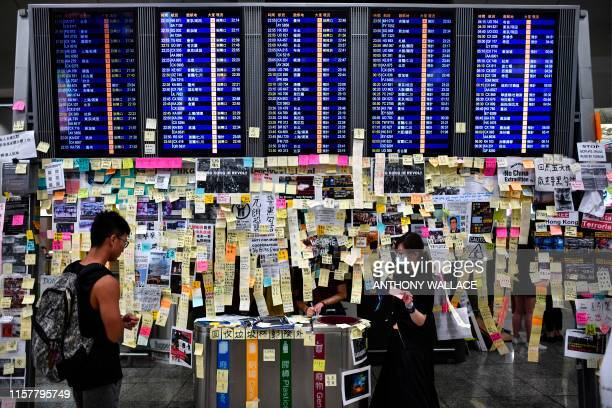 TOPSHOT Protesters add notes to a Lennon Wall under a flight display board as they rally against a controversial extradition bill at the arrivals...