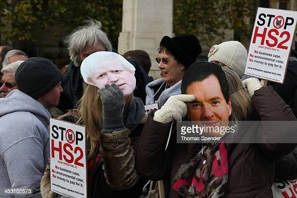 Protesters adjust masks showing the faces of Prime Minister David Cameron and Chancellor George Osborne. They were protesting against the planned HS2...