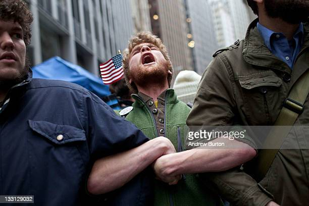 Protesters affiliated with the Occupy Wall Street movement lock arms at the intersection of Exchange Place and Beaver Street in the Financial...