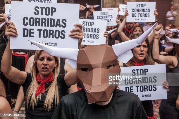 Protesters against animal cruelty in bull fightings before San Fermin celebrations in Pamplona Spain Banner says quotstop bullfightingsquot and some...