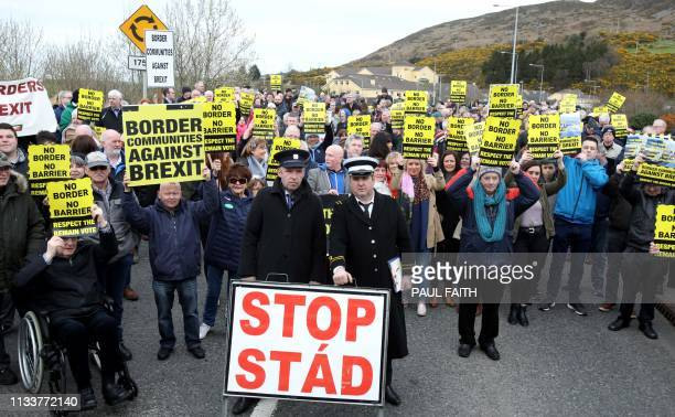 Protesters against any border between Ireland and Northern Ireland because of Brexit hold placards at the Carrickcarnan border between Newry in...