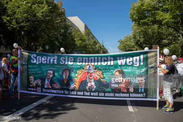 Protesters against coronavirus restrictions demonstrate with poster that shows the chancellor Angela Merkel, American business magnate Bill Gates,...