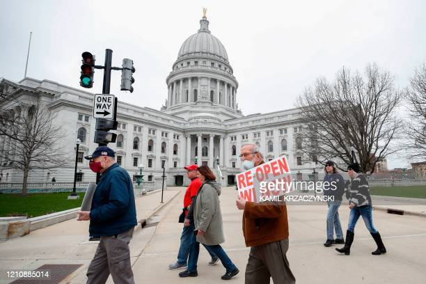 Protesters against the coronavirus shutdown rally in front of State Capitol in Madison Wisconsin on April 24 2020 The coronavirus pandemic soared...