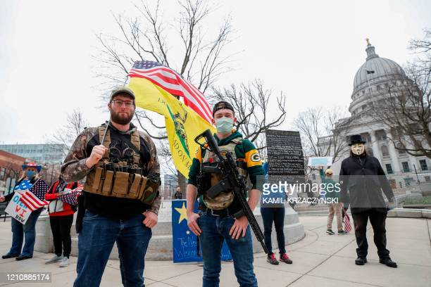 Protesters against the coronavirus shutdown stand in front of State Capitol during a rally in Madison Wisconsin on April 24 2020 Gyms hair salons and...