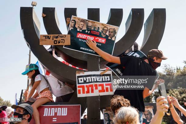 Protesters against the Israeli government, clad in masks due to the COVID-19 coronavirus pandemic, climb a Menorah sculpture and cover it with signs...