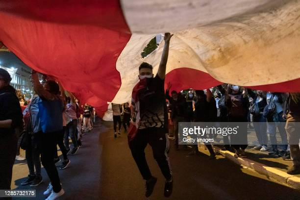 Protesters against the removal of President Martin Vizcarra march with a giant national flag as they gather in front of Palacio de Justicia as part...