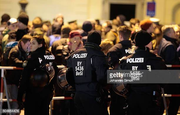 Protesters against the rightwing populist group Pegida watched by riot police demonstrate on January 11 2016 in Munich Germany Pegida and other...