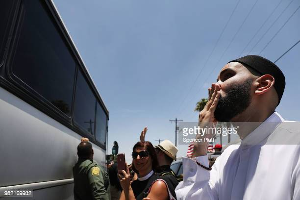 Protesters against the Trump administration's border policies wave and blow kisses to migrant children on a bus at a US Customs and Border Protection...