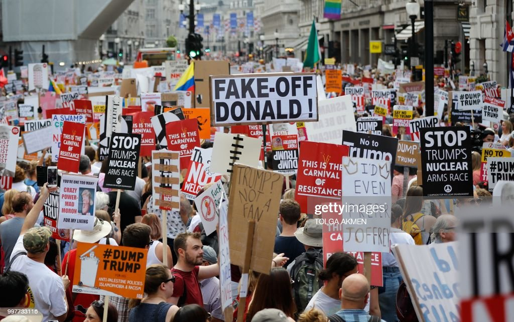 Protesters against the UK visit of US President Donald Trump gather with placards to take part in a march and rally in London on July 13, 2018. - US President Donald Trump launched an extraordinary attack on Prime Minister Theresa May's Brexit strategy, plunging the transatlantic 'special relationship' to a new low as they prepared to meet Friday on the second day of his tumultuous trip to Britain.