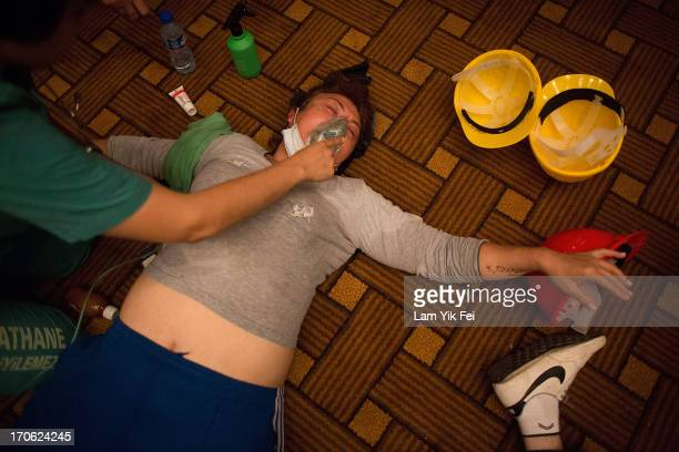 Protesters aid one another in the Divan Istanbul Hotel after riot police used tear gas to disperse the crowd near the Gezi Park on June 15 2013 in...