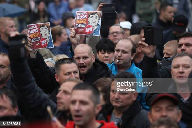 Protesters and hecklers among them supporters of the farright NPD political party hold up pieces of paper that read Merkel muss weg at the edge of an...