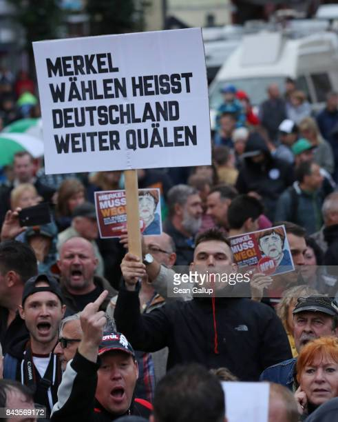 Protesters and hecklers among them supporters of the farright NPD political party hold up pieces of paper that read Merkel muss weg as another holds...