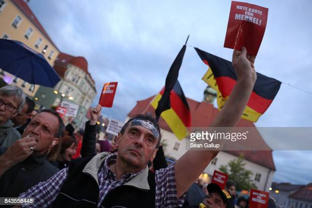 Protesters and hecklers chant Merkel muss weg and Volksverraeter while holding up red slips of paper that read Red card for Merkel at the edge of an...