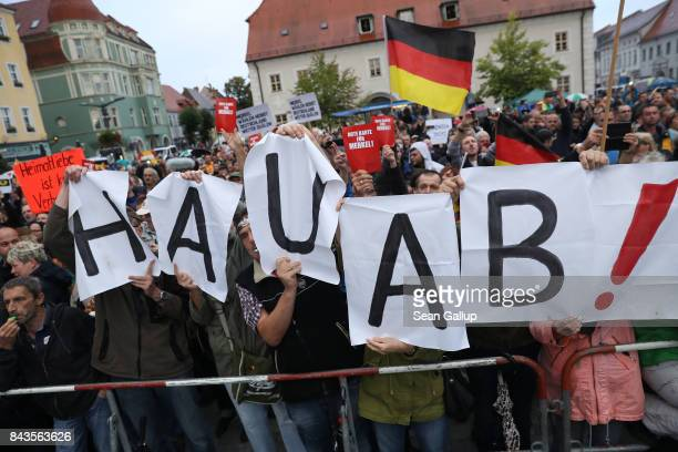 Protesters and hecklers chant Merkel muss weg and Volksverraeter while holding up letters that read Get lost at the edge of an election campaign stop...