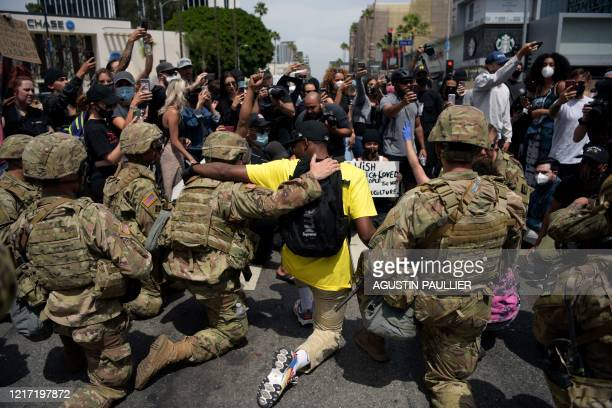 TOPSHOT Protesters and members of the Army National Guard kneel together during a demonstration over the death of George Floyd in Los Angeles on June...
